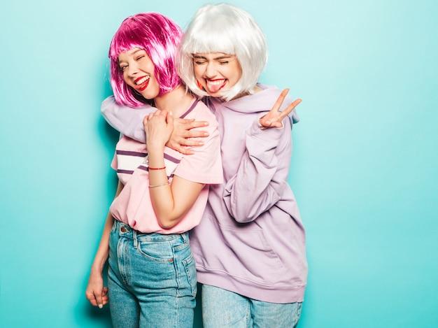 Dos chicas jóvenes y sexy hipster con pelucas y labios rojos. hermosas mujeres de moda en ropa de verano. modelos despreocupadas posando junto a la pared azul en el estudio enloqueciendo. muestra lengua