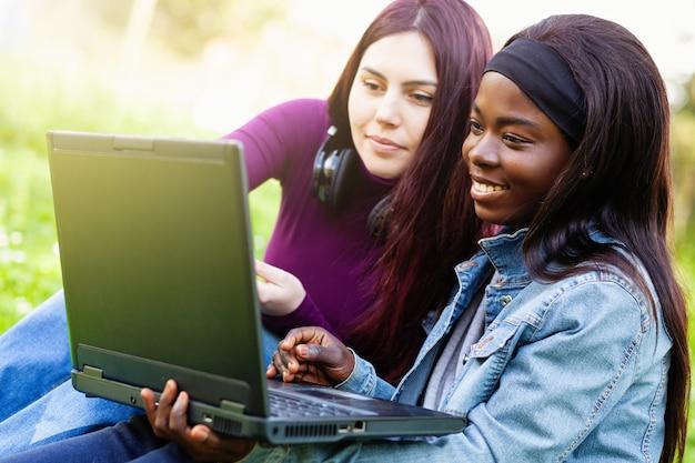 Dos chicas jóvenes sonrientes que usan la computadora portátil en el parque