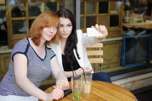 Dos chicas jóvenes tomando un autorretrato (selfie) con teléfono inteligente