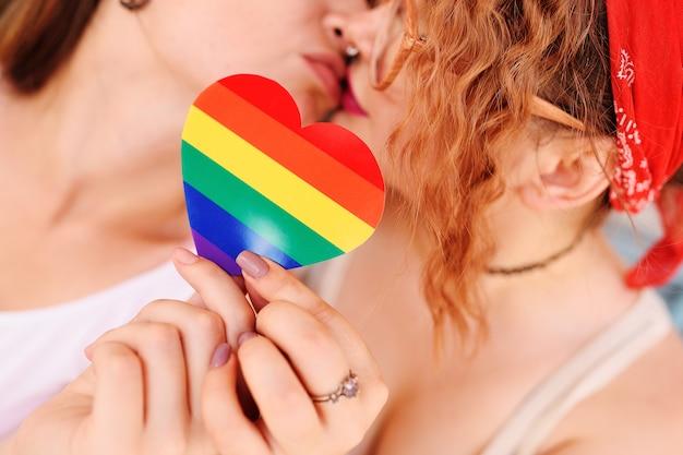Dos chicas lesbianas se besan en el fondo de un corazón con un arco iris, un símbolo de la comunidad lgbt.