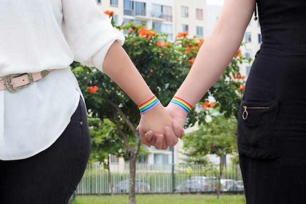 Dos chicas lesbianas cogidos de la mano con bandera del orgullo