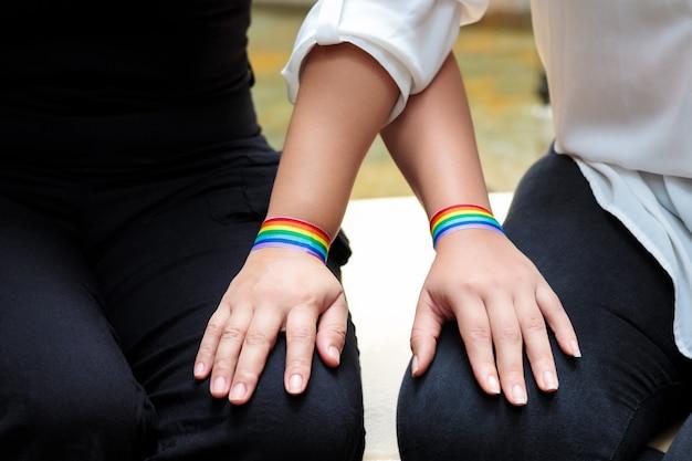 Dos chicas lesbianas sentadas y con un brazalete con la bandera del orgullo.