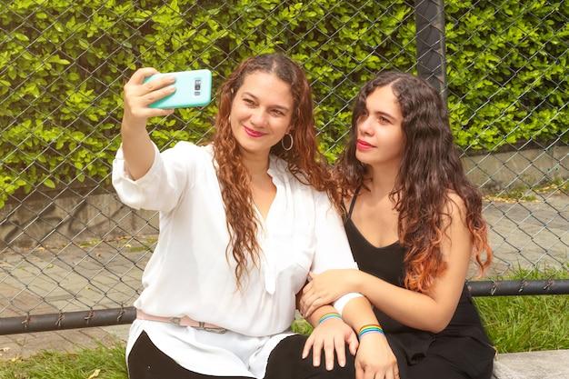 Dos chicas lesbianas tomando una foto con la bandera del orgullo en sus manos
