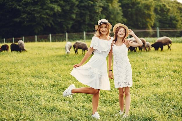 Dos chicas lindas en un campo con cabras