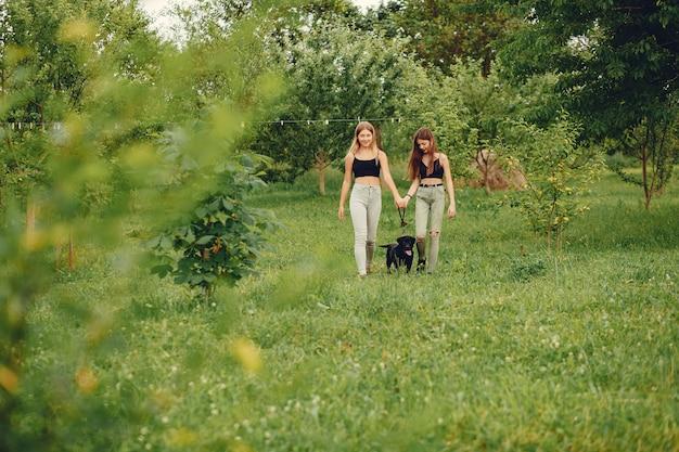 Dos chicas lindas en un parque de verano con un perro