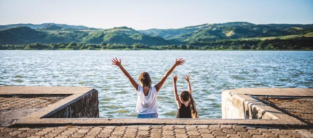 Dos chicas con las manos levantadas de pie junto al río