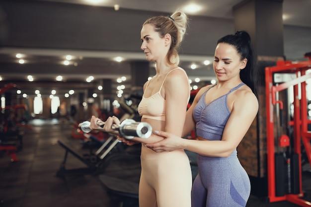 Dos chicas de mediana edad participan en el gimnasio. la entrenadora ayuda en el entrenamiento. levantando la barra para bíceps