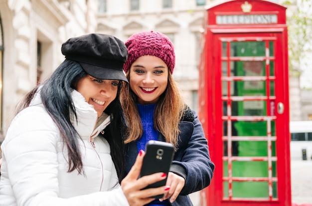 Dos chicas miran el teléfono móvil en una calle de londres con una cabina de teléfono roja en el fondo.
