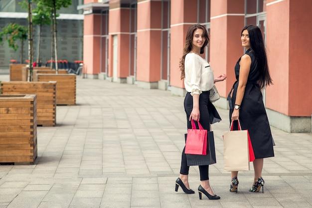 Dos chicas mirando a la cámara y sosteniendo paquetes cerca del centro comercial.