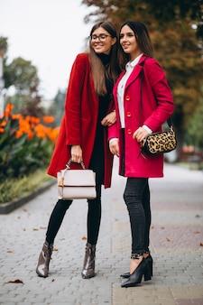 Dos chicas en modelos de abrigos rojos.