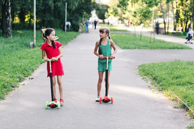 Dos chicas montando patinete en el parque