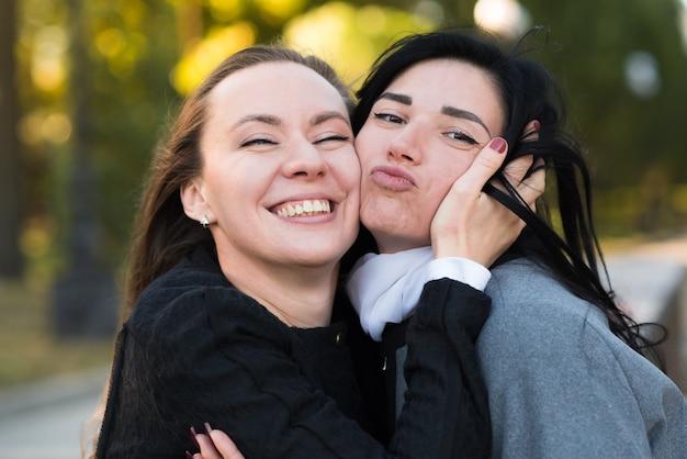 Dos chicas morenas caucásicas se abrazan en el soleado parque de otoño. feliz pareja de lesbianas, lgbt, lgbtq.