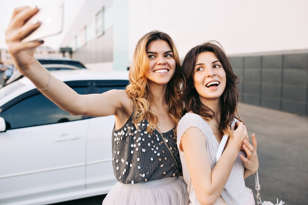 Dos chicas muy de moda haciendo selfie-retrato en el estacionamiento.