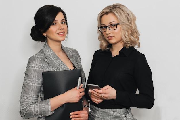 Dos chicas de negocios con sonrisas y documentos atractivos y teléfono móvil