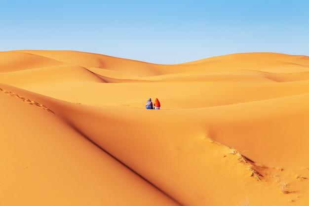 Dos chicas con pañuelos en la cabeza en el desierto del sahara.