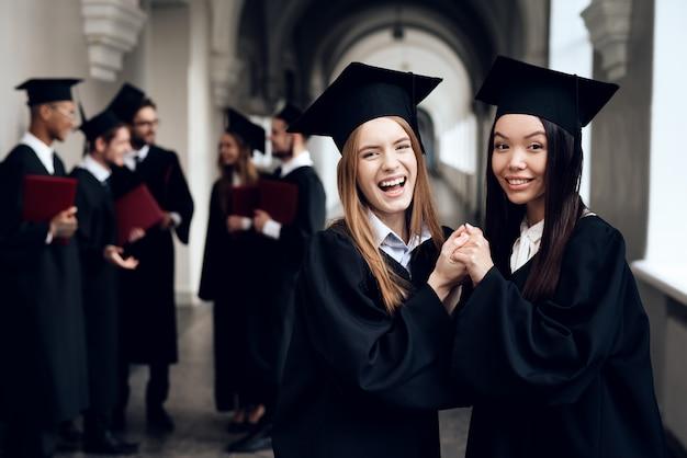Dos chicas en el pasillo de la universidad en sus túnicas.