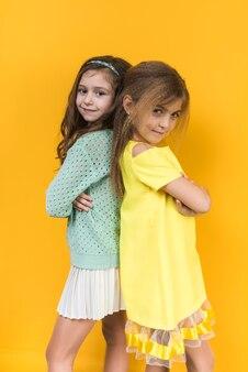 Dos chicas de pie con los brazos cruzados