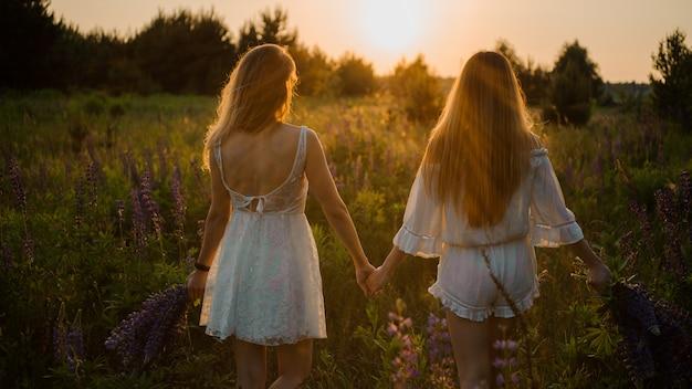 Dos chicas de pie en el campo con ramos de flores de color púrpura