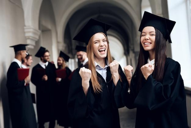 Dos chicas posan en el pasillo de la universidad.