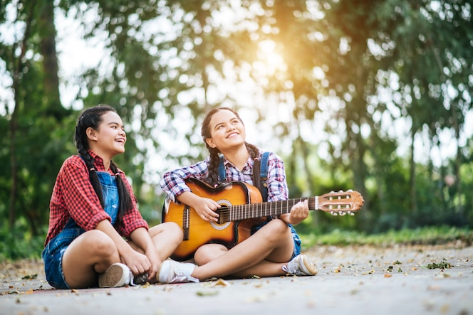 Dos chicas relajarse tocando la guitarra y cantar una canción
