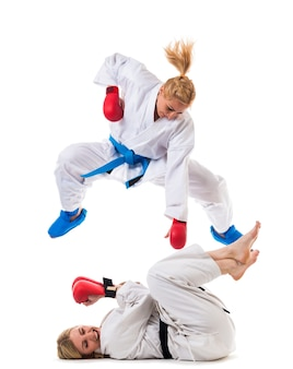 Dos chicas en ropa deportiva blanca pelea de entrenamiento en guantes de boxeo
