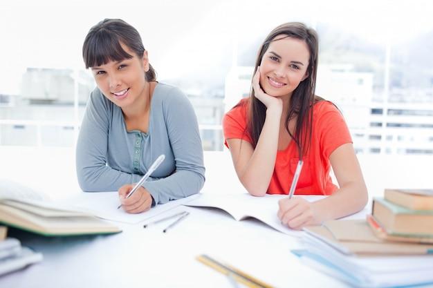 Dos chicas sonriendo y mirando a la cámara mientras hacen la tarea