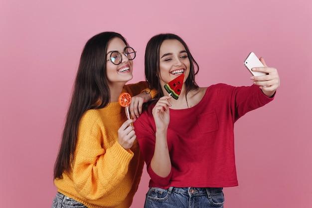 Dos chicas sonrientes toman selfie en sus teléfonos posando con piruletas