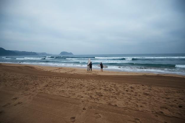 Dos chicas surfistas irreconocibles con sus longboards permanecen en la orilla del océano y observan las olas temprano en la mañana, vistiendo trajes de neopreno completos y listas para surfear