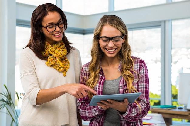 Dos chicas trabajan en la oficina en tableta