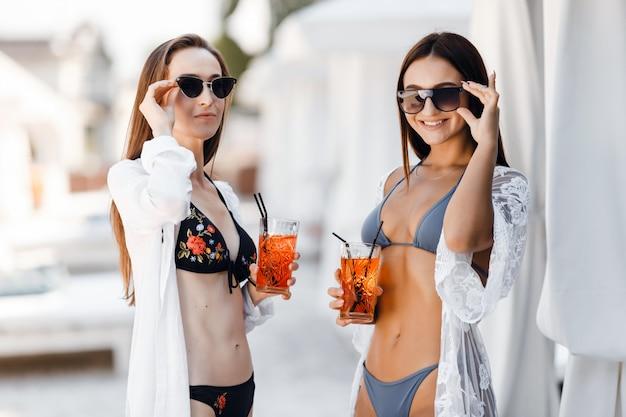Dos chicas en traje de baño posando con bebida