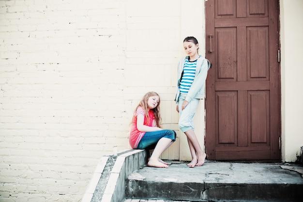 Dos chicas tristes en la pared de fondo