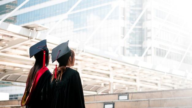 Dos chicas en vestidos negros de pie miran hacia el cielo con graduados felices.