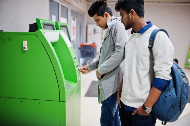 Dos chicos asiáticos sacan efectivo de un cajero automático verde