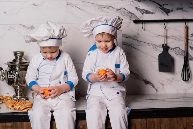Dos chicos gemelos lindos sentados en el suelo y comiendo felizmente alimentos saludables, cocineros jóvenes