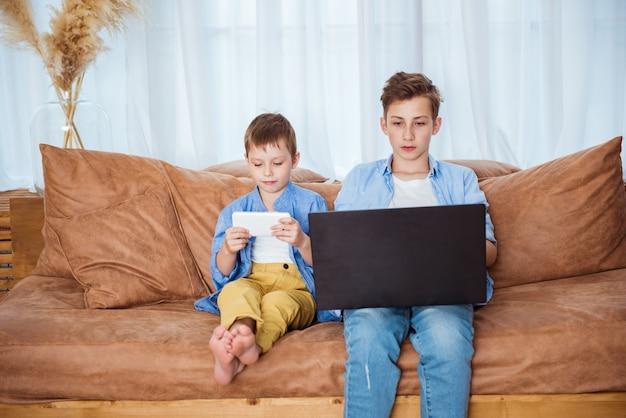 Dos chicos guapos que miran aparatos y se comunican con sus familiares en línea a través de internet