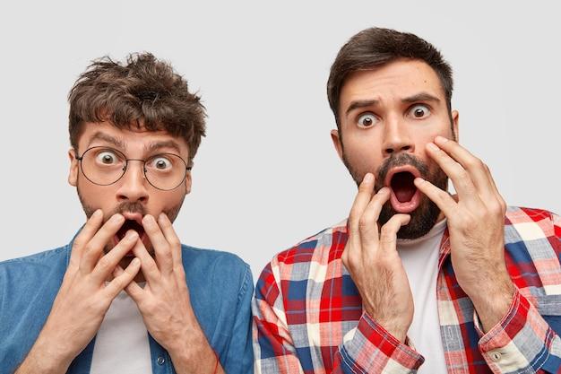 Dos chicos jóvenes barbudos asombrados miran fijamente a la cámara con expresiones nerviosas asustadas, cierran la boca, reaccionan ante algo horrible, posan contra la pared blanca