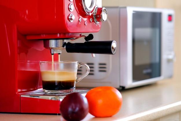 Dos chorros de café expreso en la máquina de café expreso se vierten en una taza transparente