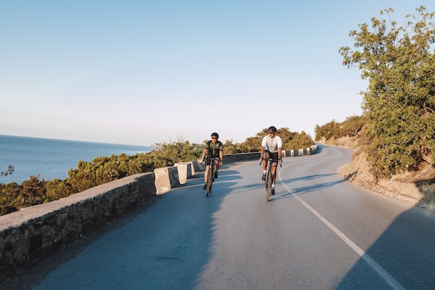 Dos ciclistas profesionales masculinos montando sus bicicletas de carreras en la mañana juntos en la carretera costera