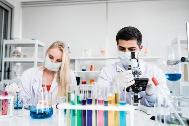 Dos científicos están trabajando sosteniendo mirando el tubo de ensayo con muestra en un científico de laboratorio de química