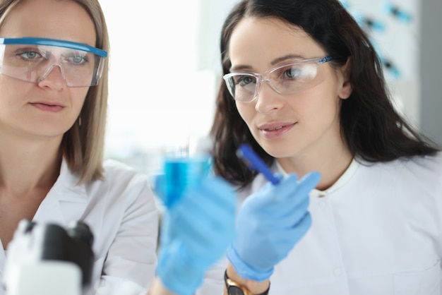 Dos científicos con gafas miran un tubo de ensayo de líquido. desarrollo de nuevo concepto de sustancias