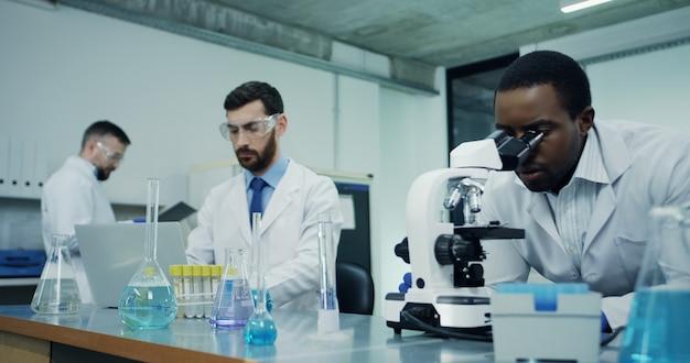 Dos científicos de laboratorio masculinos multiétnicos hablando mientras uno trabaja en el microscopio y asesora al otro que prueba algo en los tubos.