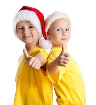 Dos cildl sonriente con pulgar hacia arriba firmar en sombreros de santa, aislado en blanco