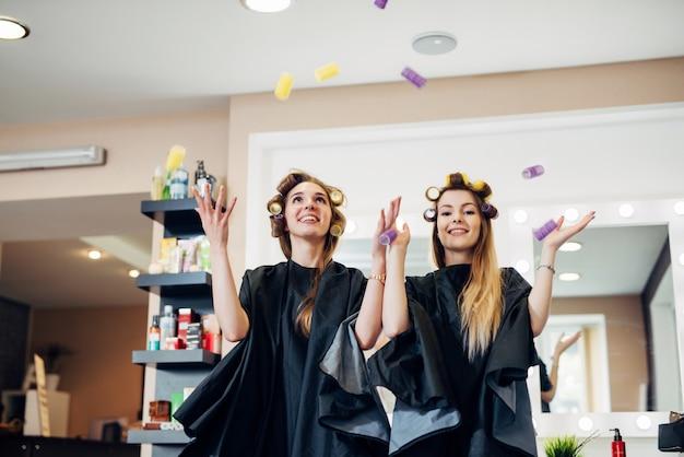 Dos clientas de salón de belleza de pie en rulos divirtiéndose jugando riendo