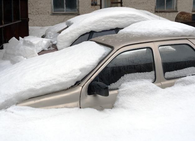 Dos coches completamente enterrados en la nieve.