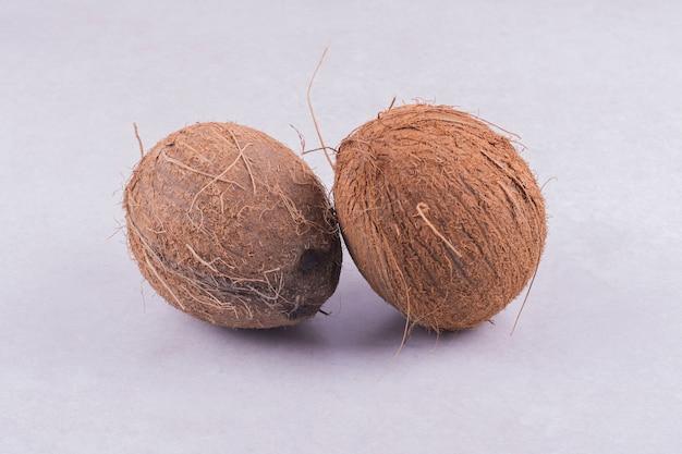 Dos cocos aislados sobre superficie blanca.