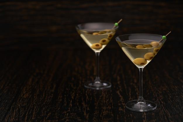 Dos cócteles de bebidas alcohólicas con aceitunas verdes.