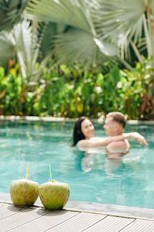 Dos cócteles de coco en el borde de la piscina, pareja bailando y abrazándose en el agua