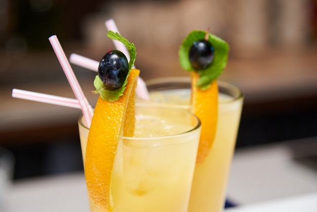 Dos cócteles de naranja con una rodaja de naranja, oliva y menta.