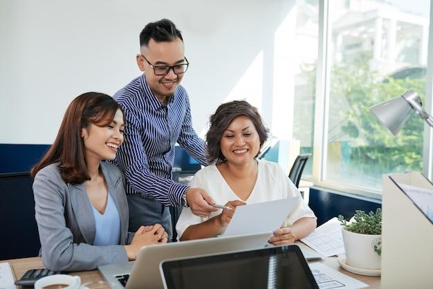Dos colegas asiáticos femeninos y uno masculino discutiendo documentos juntos en la oficina