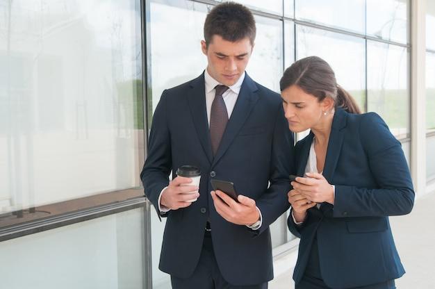Dos colegas enfocados con teléfonos que comparten información.